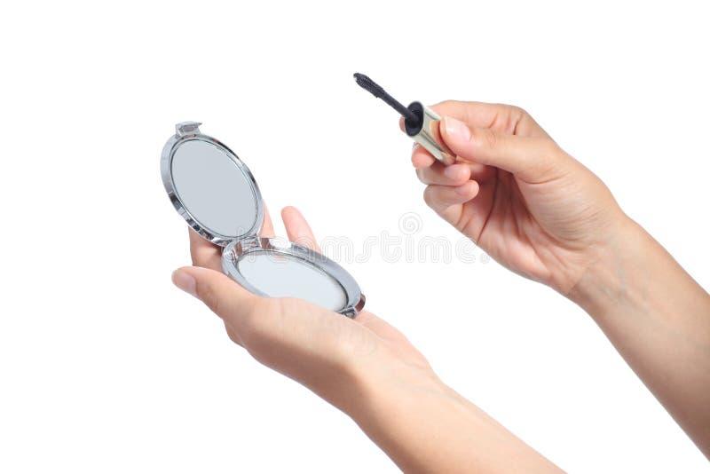 A mulher entrega manter um espelho de mão e um rímel do chicote prontos para compor imagens de stock