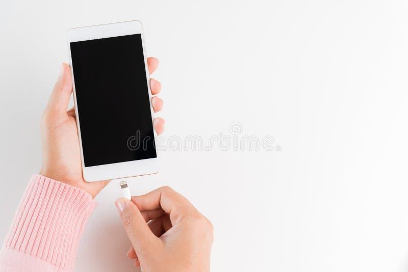 A mulher entrega o carregador de conexão ao smartphone na parte traseira branca da tabela foto de stock royalty free