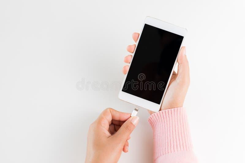 A mulher entrega o carregador de conexão ao smartphone na tabela branca fotografia de stock