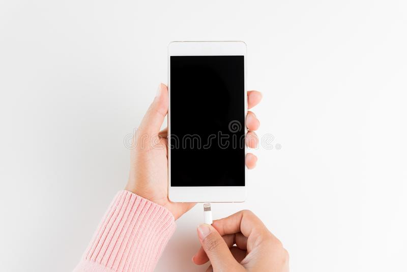 A mulher entrega o carregador de conexão ao smartphone na tabela branca imagens de stock royalty free