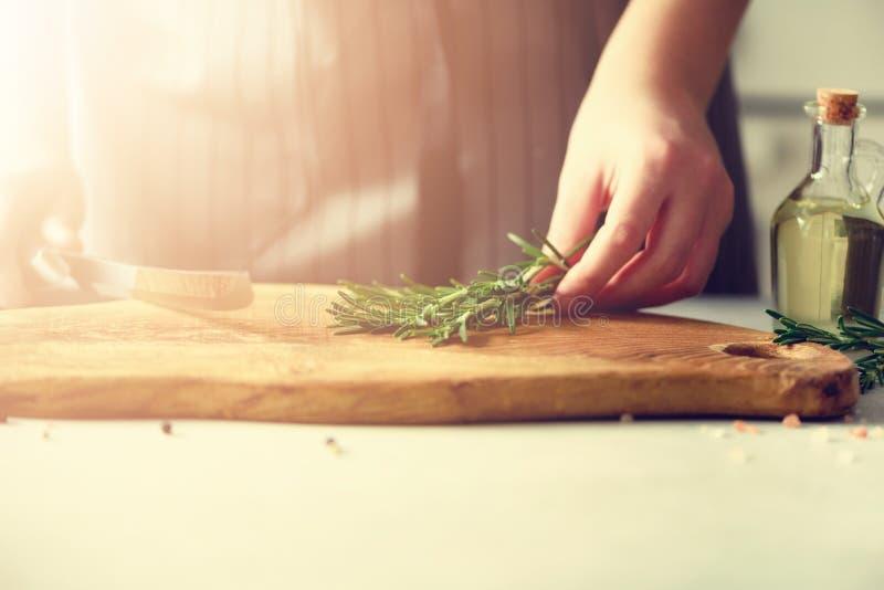 A mulher entrega o corte de alecrins verdes frescos na placa de desbastamento de madeira na cozinha branca, interior Copie o espa imagens de stock royalty free