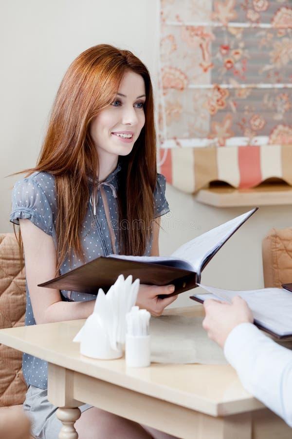 A mulher entrega o menu para fazer um pedido fotografia de stock