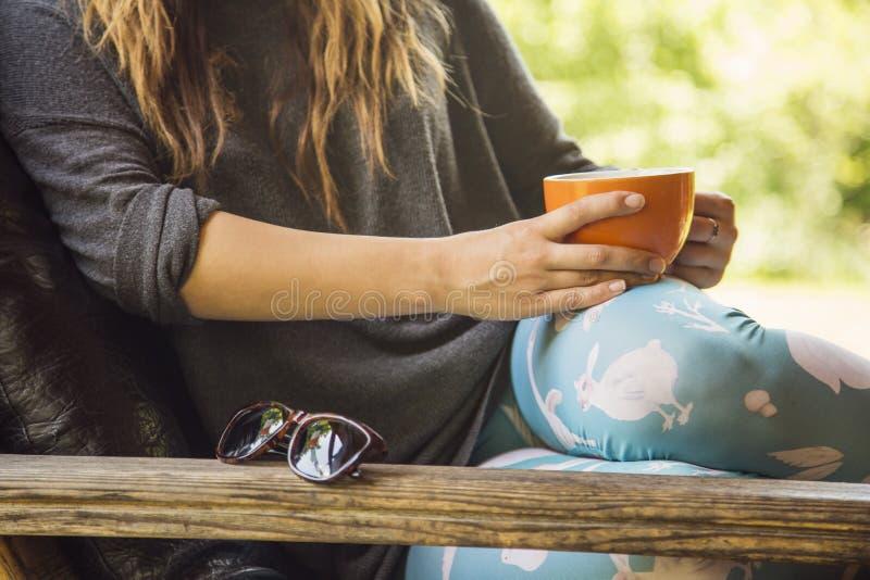A mulher entrega prender uma chávena de café foto de stock royalty free