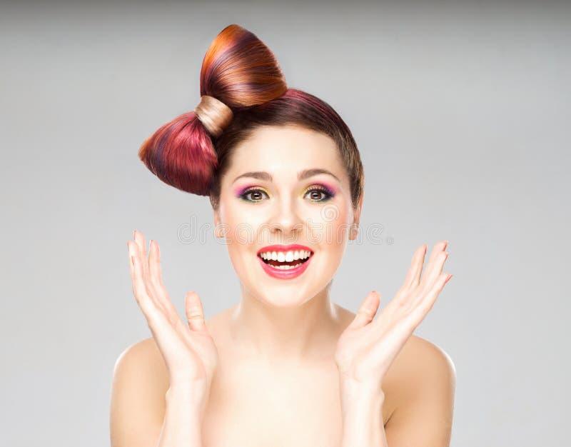 Mulher entusiasmado atrativa com um corte de cabelo da curva e uma composição colorida no fundo cinzento imagem de stock royalty free