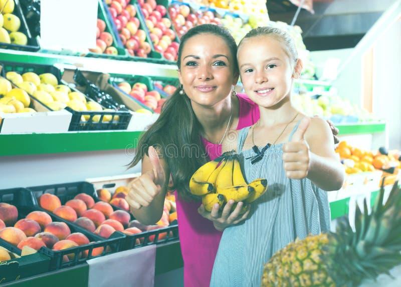 Mulher entusiasmado com a filha no mercado de fruto fotografia de stock royalty free
