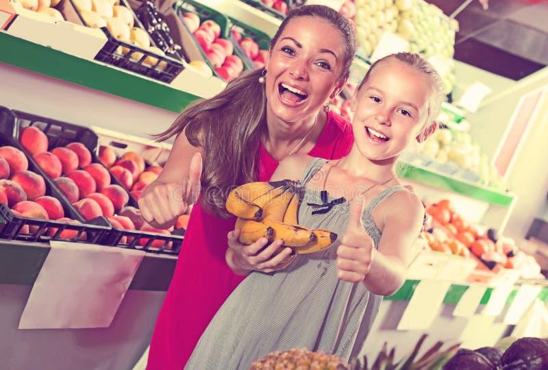 Mulher entusiasmado com a filha no mercado de fruto imagens de stock