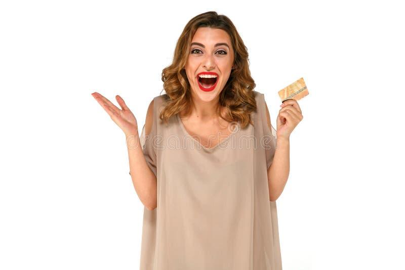 A mulher entusiasmado com o cartão de crédito do ouro à disposição no branco isolou o fundo foto de stock