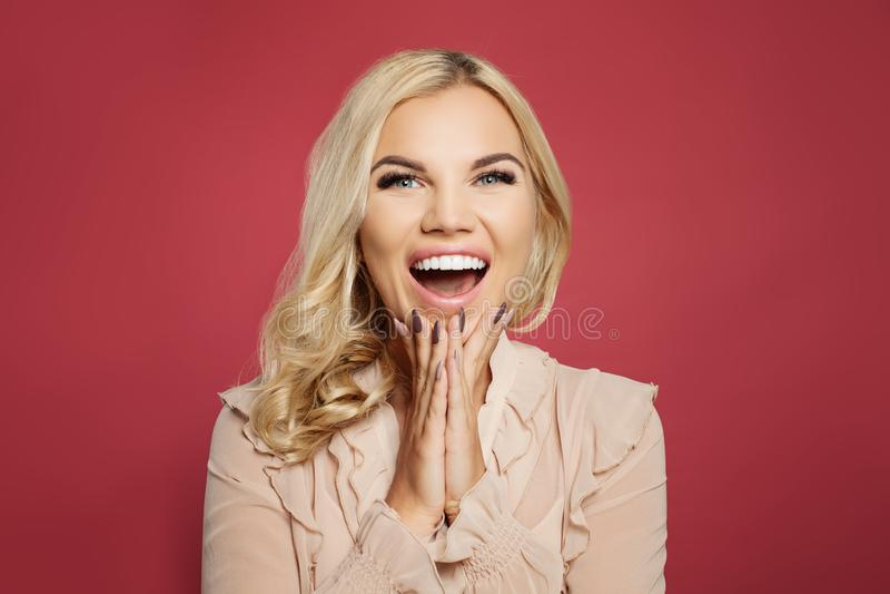 Mulher entusiasmado feliz bonita que ri e que grita no fundo cor-de-rosa colorido Menina surpreendida com boca aberta fotos de stock royalty free