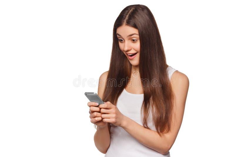 Mulher entusiasmado feliz que olha o telefone celular quando envio de mensagem de texto, isolado no fundo branco fotos de stock