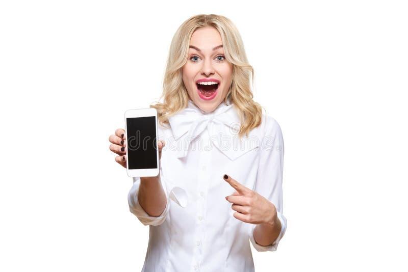 Mulher entusiasmado lindo que aponta ao telefone celular da tela vazia sobre o fundo branco, comemorando a vitória e o sucesso fotografia de stock
