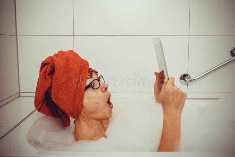 Mulher entusiasmado na banheira com tablet pc fotos de stock