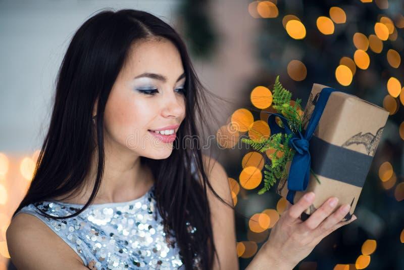 Mulher entusiasmado na noite de Natal que senta-se perto da árvore e que levanta seu presente do Natal para escutar para dentro q imagens de stock