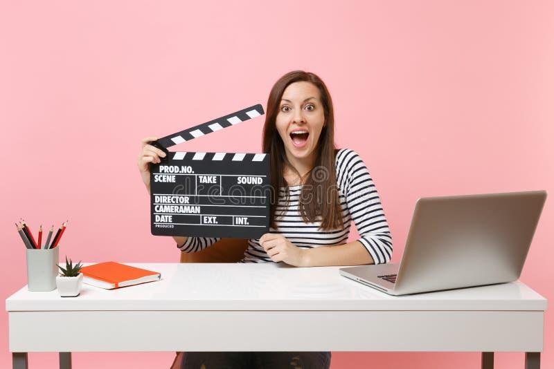 Mulher entusiasmado nova para guardar o clapperboard preto clássico da cinematografia que trabalha no quando do projeto para sent imagens de stock royalty free