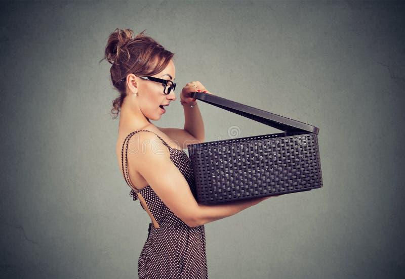 Mulher entusiasmado que abre uma caixa com uma surpresa fotografia de stock