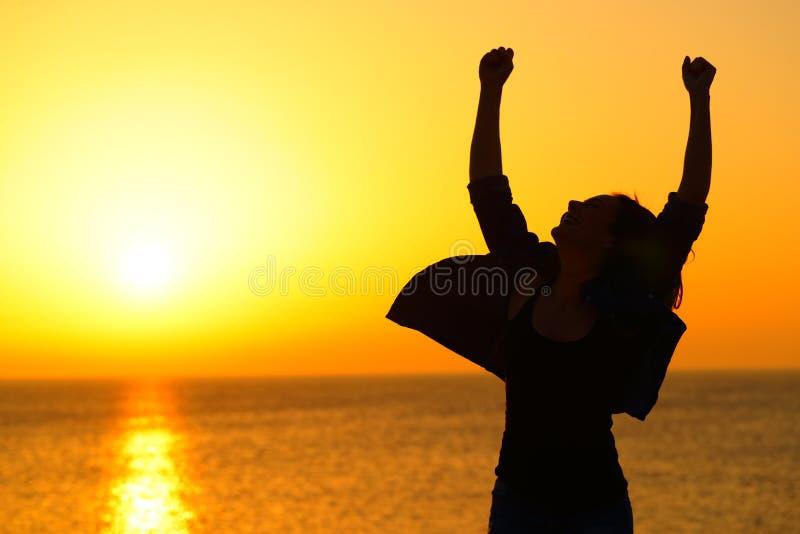 Mulher entusiasmado que comemora o sucesso no nascer do sol imagens de stock