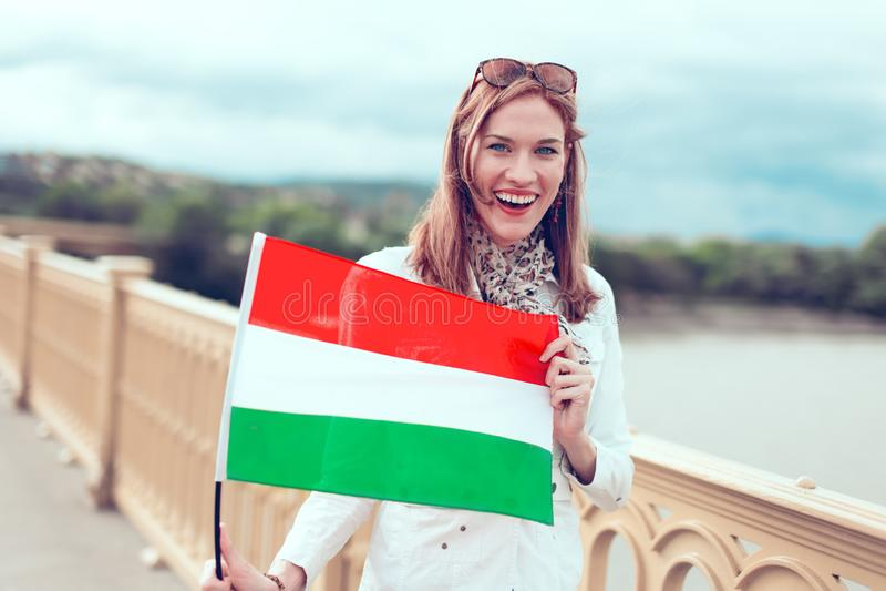 Mulher entusiasmado que guarda a bandeira húngara fora foto de stock