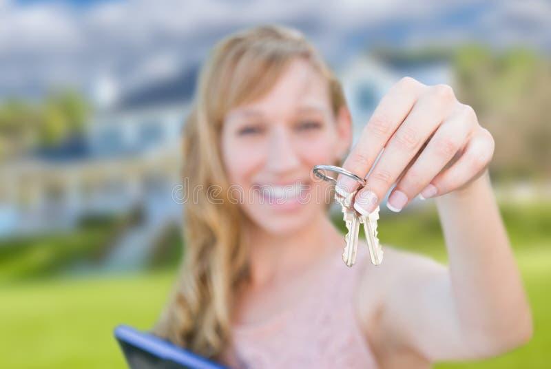 Mulher entusiasmado que guarda chaves da casa na frente da casa nova agradável fotografia de stock