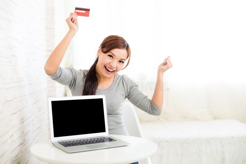 Mulher entusiasmado que guarda o cartão de crédito com laptop imagens de stock