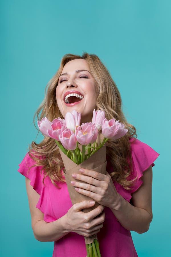 Mulher entusiasmado que guarda o ramalhete de flores da mola imagens de stock royalty free