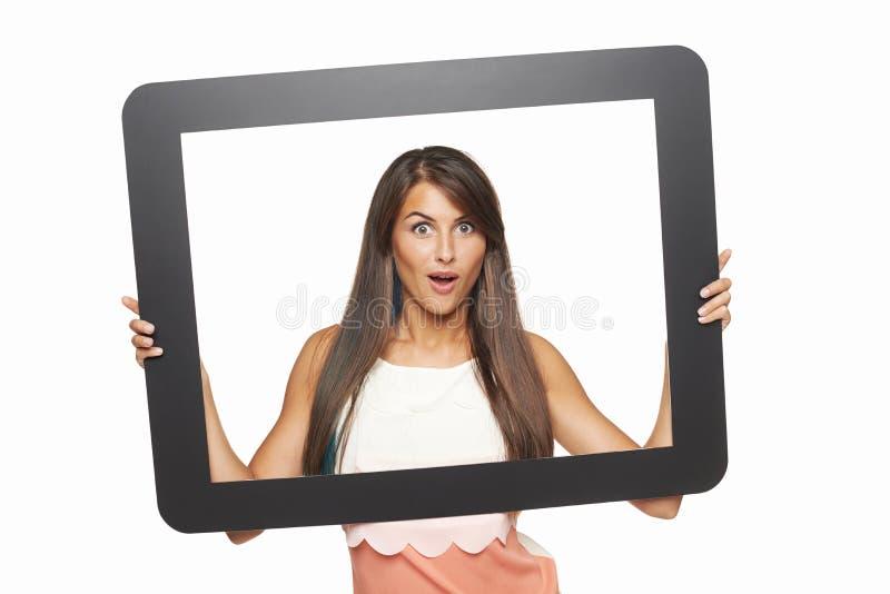 Mulher entusiasmado que olha através do quadro da tabuleta imagens de stock