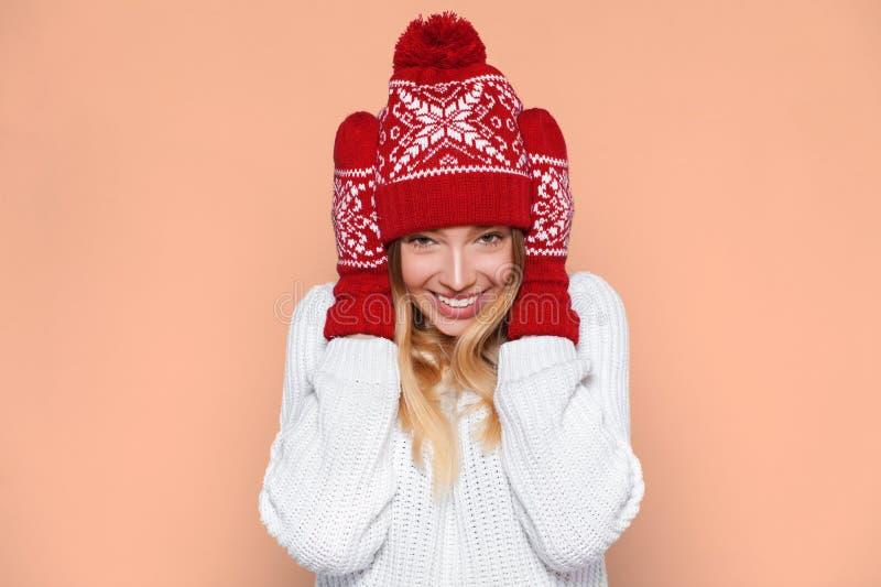 Mulher entusiasmado que olha lateralmente no excitamento Menina do Natal feliz que veste o chapéu feito malha e os mitenes mornos imagem de stock