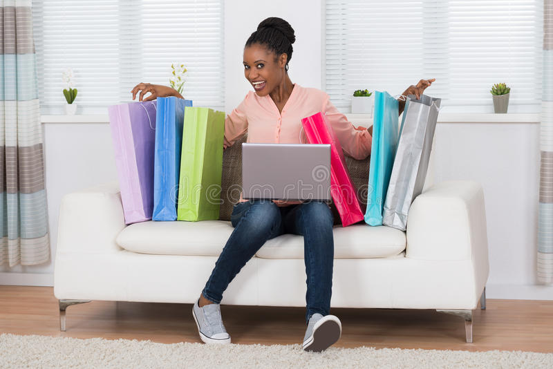 Mulher entusiasmado que senta-se em sacos de Sofa With Laptop And Shopping fotografia de stock royalty free
