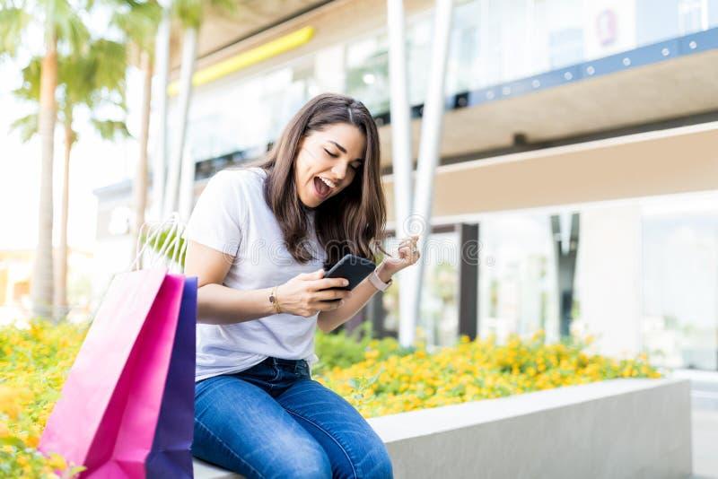 Mulher entusiasmado que usa Smartphone por sacos de compras fora da alameda fotos de stock