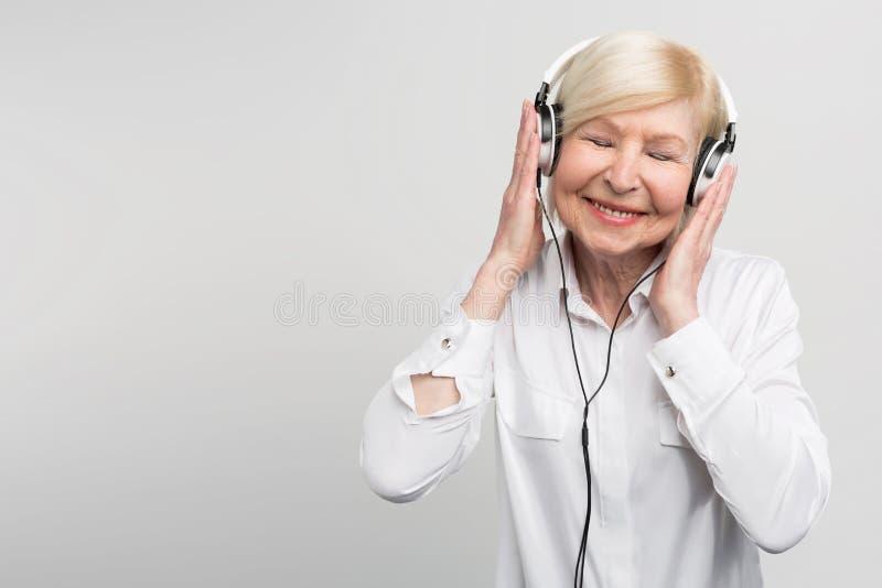 Mulher envelhecida alegre que escuta a música nos fones de ouvido Está apreciando o momento No fundo branco imagem de stock