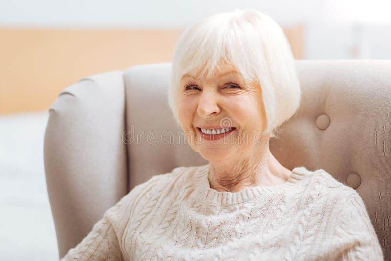 Mulher envelhecida bonito adorável que sente feliz ao sentar-se e ao sorrir fotos de stock
