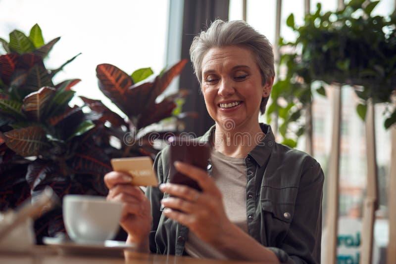 Mulher envelhecida feliz com telefone e cartão de crédito imagem de stock