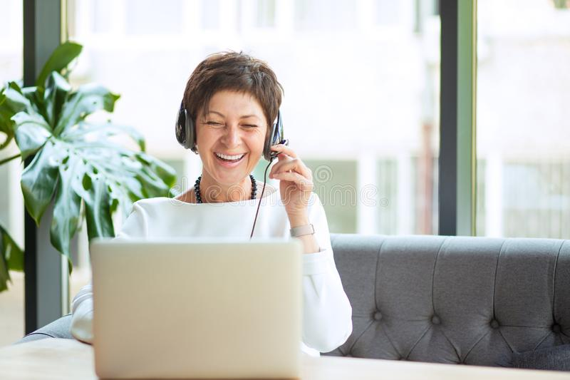 Mulher envelhecida feliz nos auriculares e no portátil na tabela fotos de stock royalty free