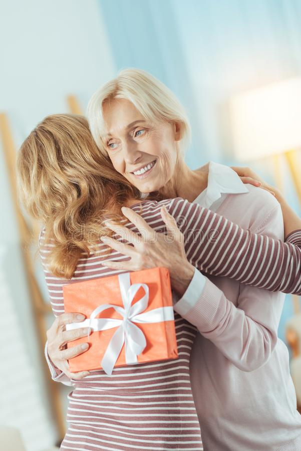 Mulher envelhecida feliz que guarda um presente brilhante ao abraçar seu parente imagens de stock