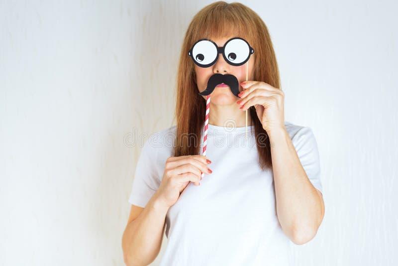 Mulher envelhecida média atrativa que tem o divertimento com um bigode falsificado e vidros fotografia de stock royalty free