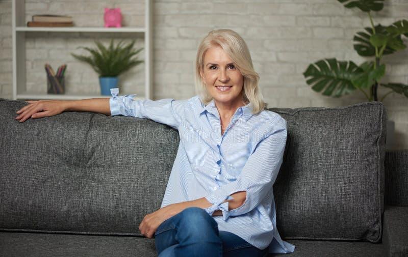 A mulher envelhecida média bonita está sentando-se em um sofá em casa fotografia de stock