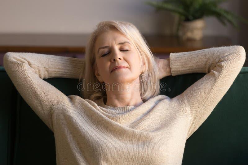 Mulher envelhecida média calma que relaxa apreciando o fim de semana no sofá confortável foto de stock