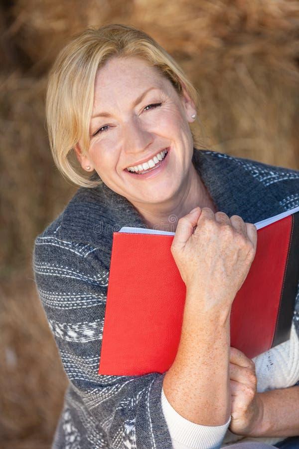 Mulher envelhecida média de riso feliz que lê um livro ou um diário imagens de stock