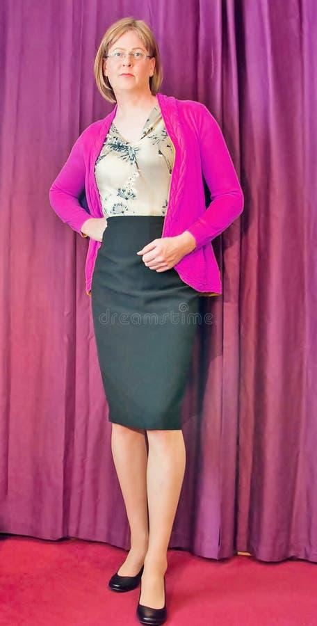 Mulher envelhecida média espertamente vestida que veste um casaco de lã cor-de-rosa e uma saia preta do lápis imagem de stock