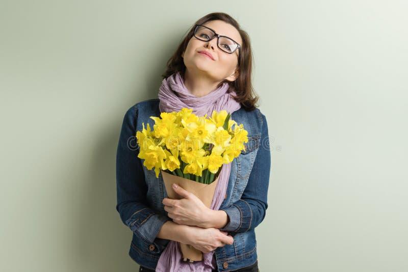 Mulher envelhecida média feliz com o ramalhete de flores amarelas, fundo verde da parede fotos de stock