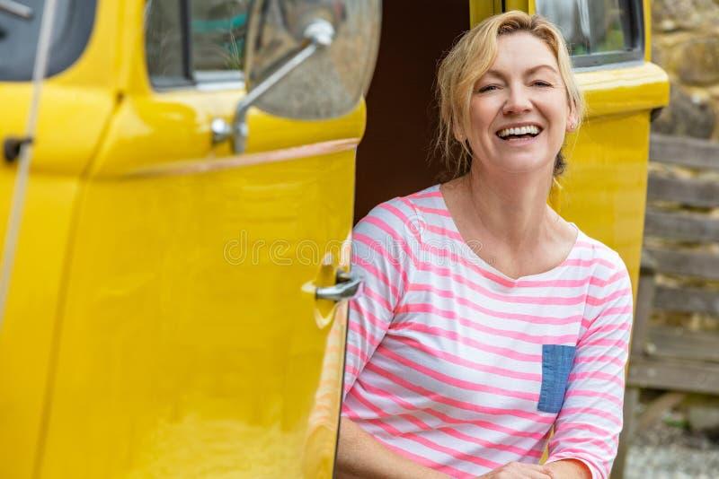 Mulher envelhecida média feliz que senta-se no campista Van ou no ônibus fotografia de stock