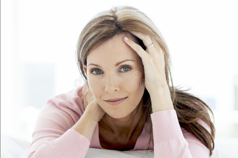 Mulher envelhecida média lindo que encontra-se para baixo olhando a câmera - retrato imagem de stock