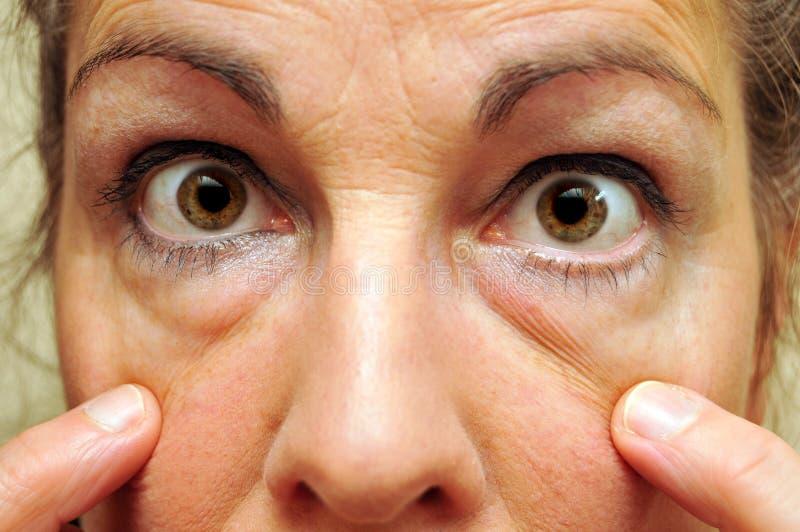 Mulher envelhecida média que aponta em seu close up dos olhos imagem de stock