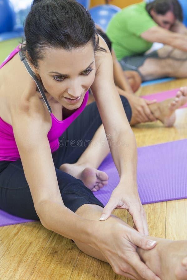 Mulher envelhecida média que estica a ioga praticando imagem de stock royalty free