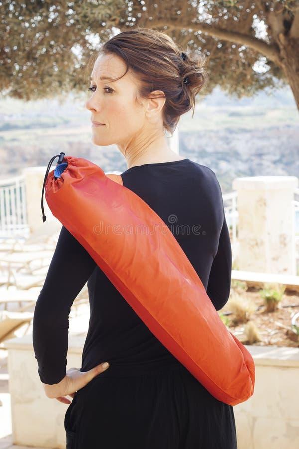 Mulher envelhecida meio com esteira da ioga imagem de stock