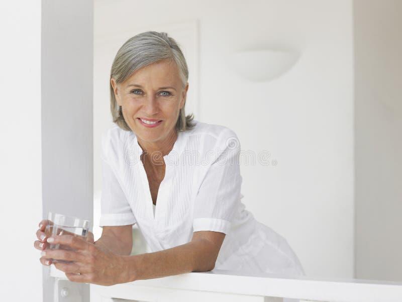 Mulher envelhecida meio com vidro de água na varanda fotos de stock