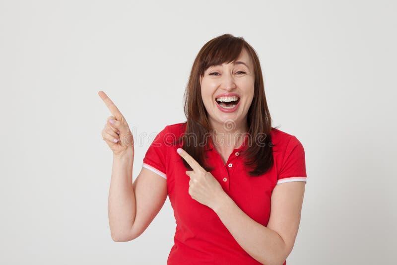 Mulher envelhecida meio de riso que mostra algo por seus dedos isolados no branco Copie o espaço Tempo do divertimento do verão fotografia de stock royalty free