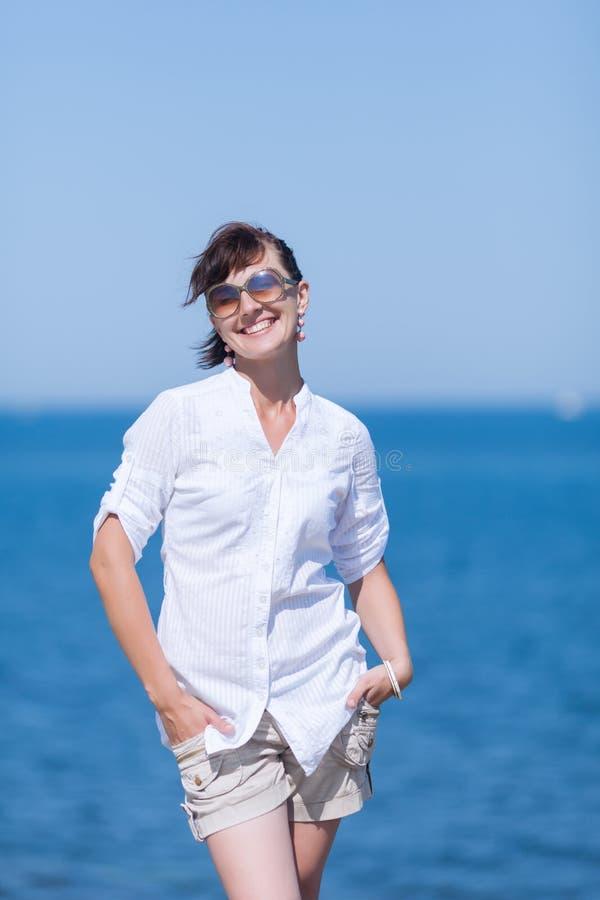 A mulher envelhecida meio está com mãos em uns bolsos contra o mar imagens de stock royalty free