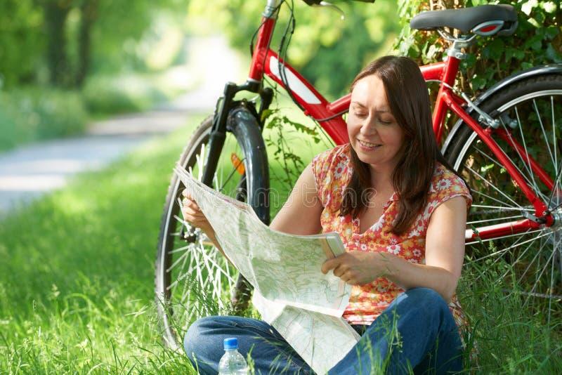 Mulher envelhecida meio no passeio do ciclo no mapa da leitura do campo imagens de stock royalty free
