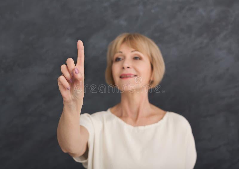 Mulher envelhecida meio que aponta no objeto invisível fotografia de stock