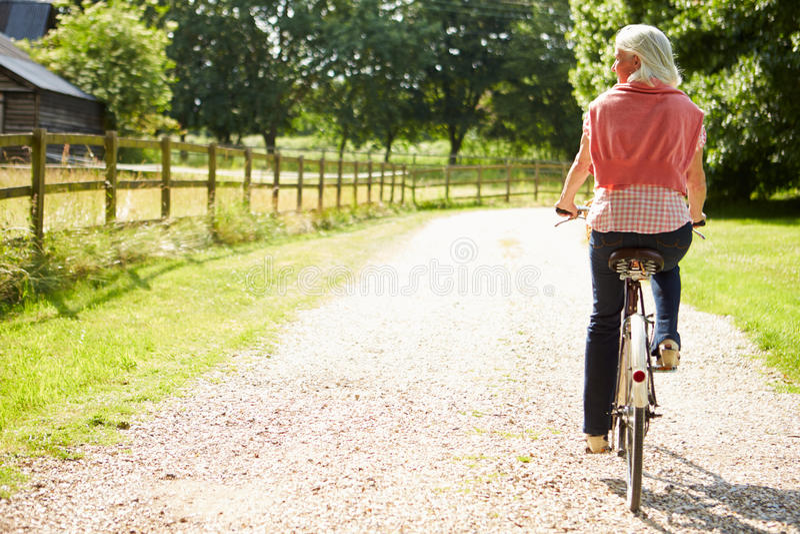 Mulher envelhecida meio que aprecia o passeio do ciclo do país fotografia de stock royalty free