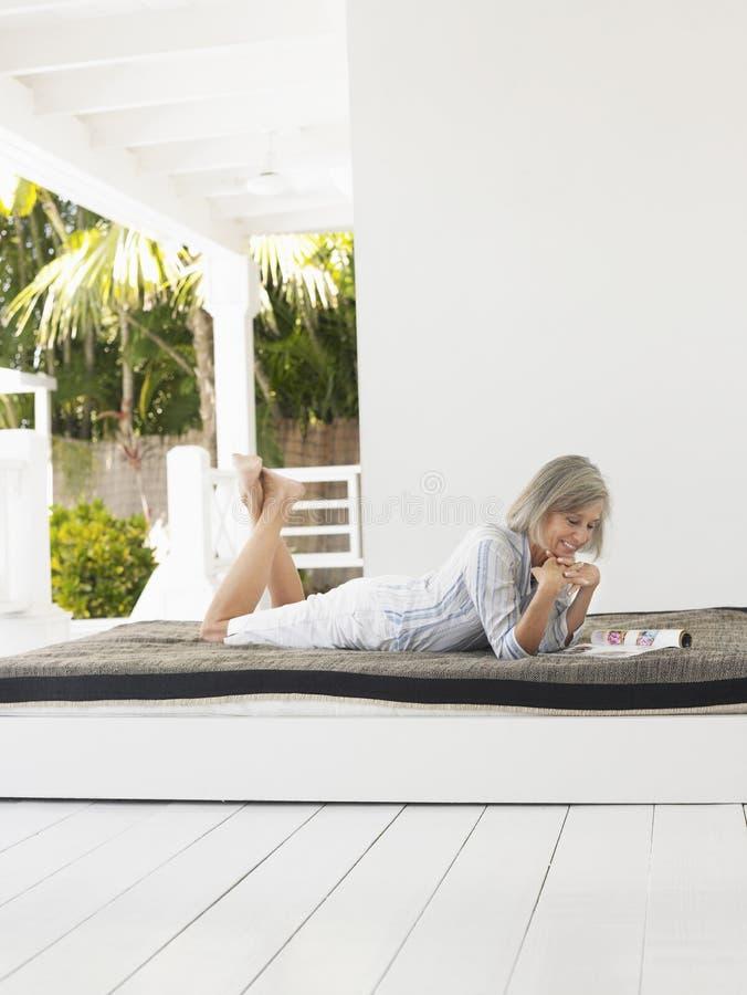 Mulher envelhecida meio que encontra-se no Daybed na varanda fotografia de stock royalty free
